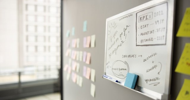 A whiteboard hangs on a wall next to sticky notes, populated with digital transformation strategy planning