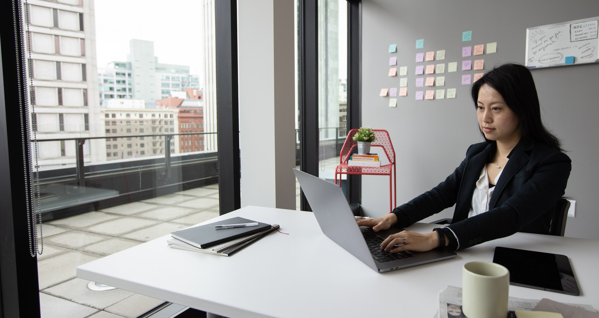 An executive works on a laptop in her office to build a successful digital transformation strategy