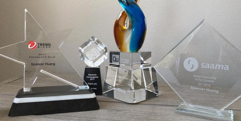 Sales Leader Spencer Huang's Awards – Geometric shaped glass trophies on a shelf against a white wall.